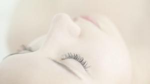 幹細胞エステの施術をうけながら気持ち良さそうに目を閉じて若返りをイメージしている女性
